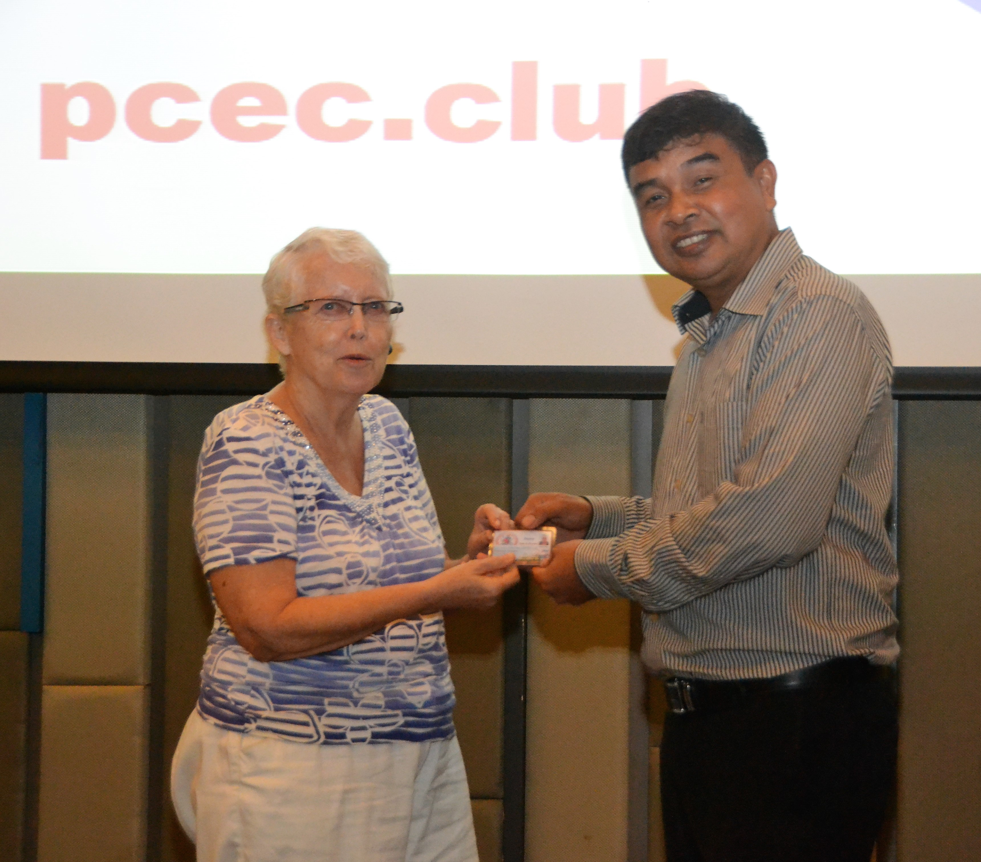 Chatchai Sriphoornthe, Deputy Chief for Banglamung District, presents Club member Donna Westendorf with her Commemoration Card from the District.