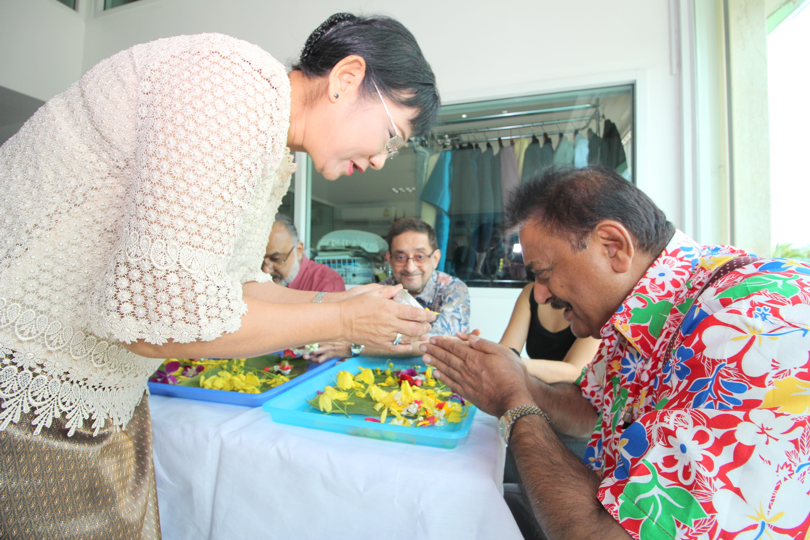 Rotary District Governor-elect pours lustral water on the hands of PDG Peter Malhotra who gives his blessings in return.