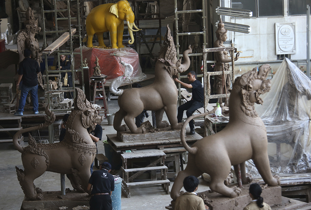 Artisans working on sculptures of deities and creatures from ancient Indian epics to decorate the royal crematorium for the late King Bhumibol Adulyadej at the Office of Traditional Arts in Nakhon Pathom province. (AP Photo/Sakchai Lalit)