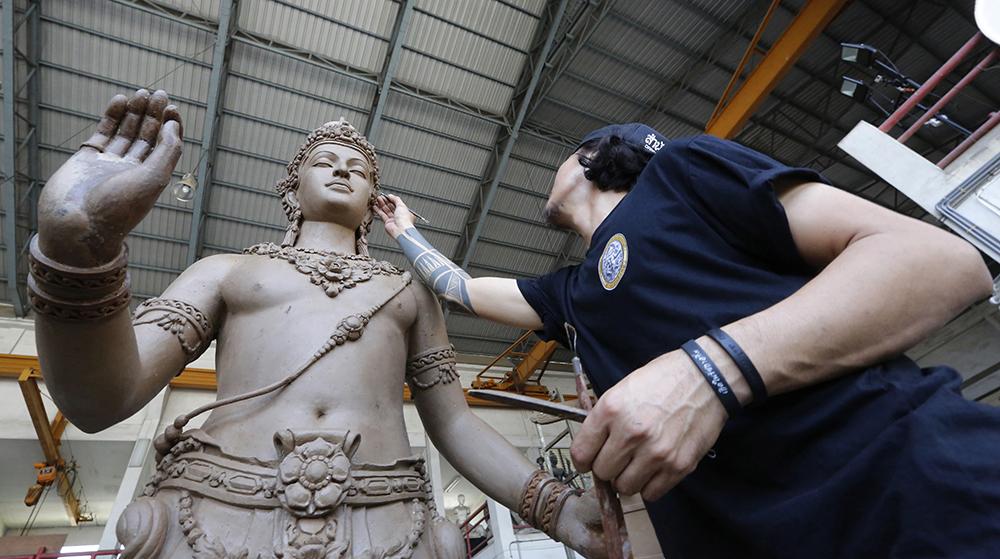 An artist sculpts deities and creatures from ancient Indian epics to decorate the royal crematorium. (AP Photo/Sakchai Lalit)