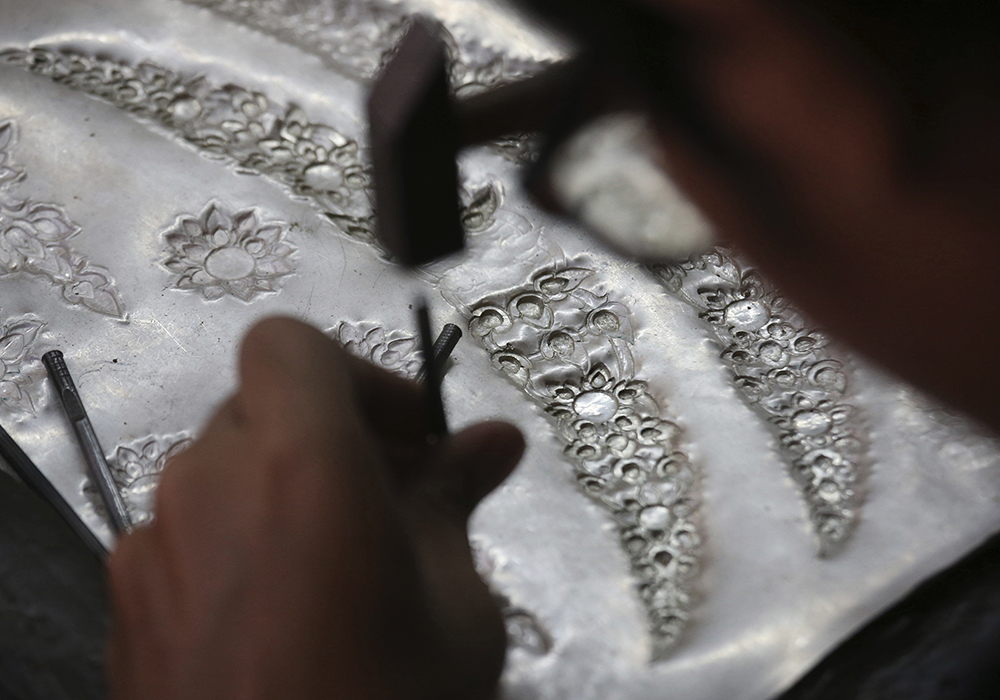 A student volunteer hammers designs into silver plates to decorate the royal crematorium. (AP Photo/Sakchai Lalit)