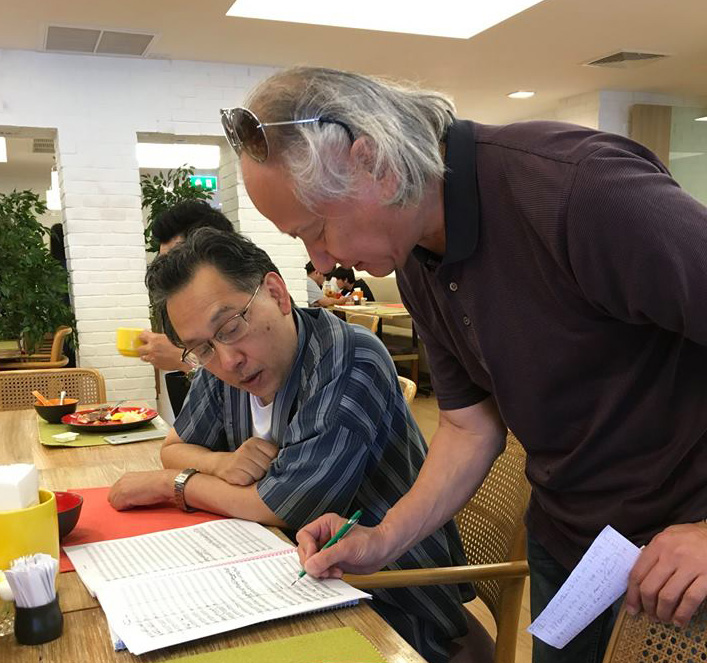 Composer Narongrit Dhamabutra (left) and conductor Hikotaro Yazaki discuss a point in the Sinfonia Chakri score.