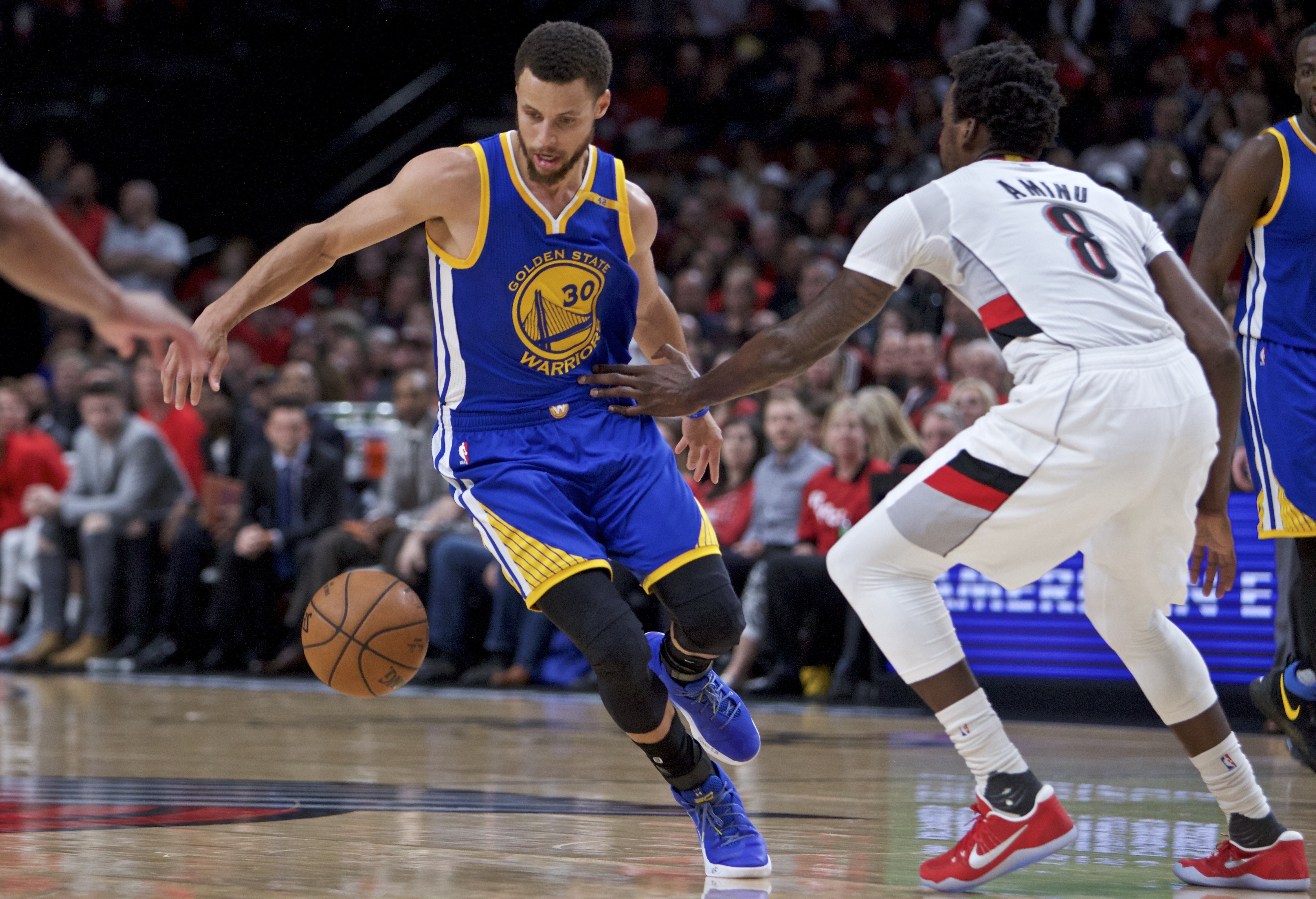 Golden State Warriors guard Stephen Curry (left) dribbles around his back past Portland Trail Blazers forward Al-Farouq Aminu during the first half of Game 4 of their NBA basketball first-round playoff series, Monday, April 24, in Portland, Ore. (AP Photo/Craig Mitchelldyer)
