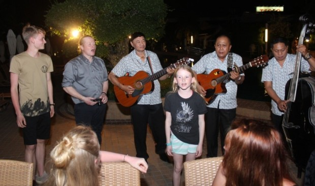 Luke Christopher Kelly, Joey Kelly and Lillian Ann Kelly singing the latest hit of the Kelly Family 'Nanana' accompanied by the Thai Garden trio.