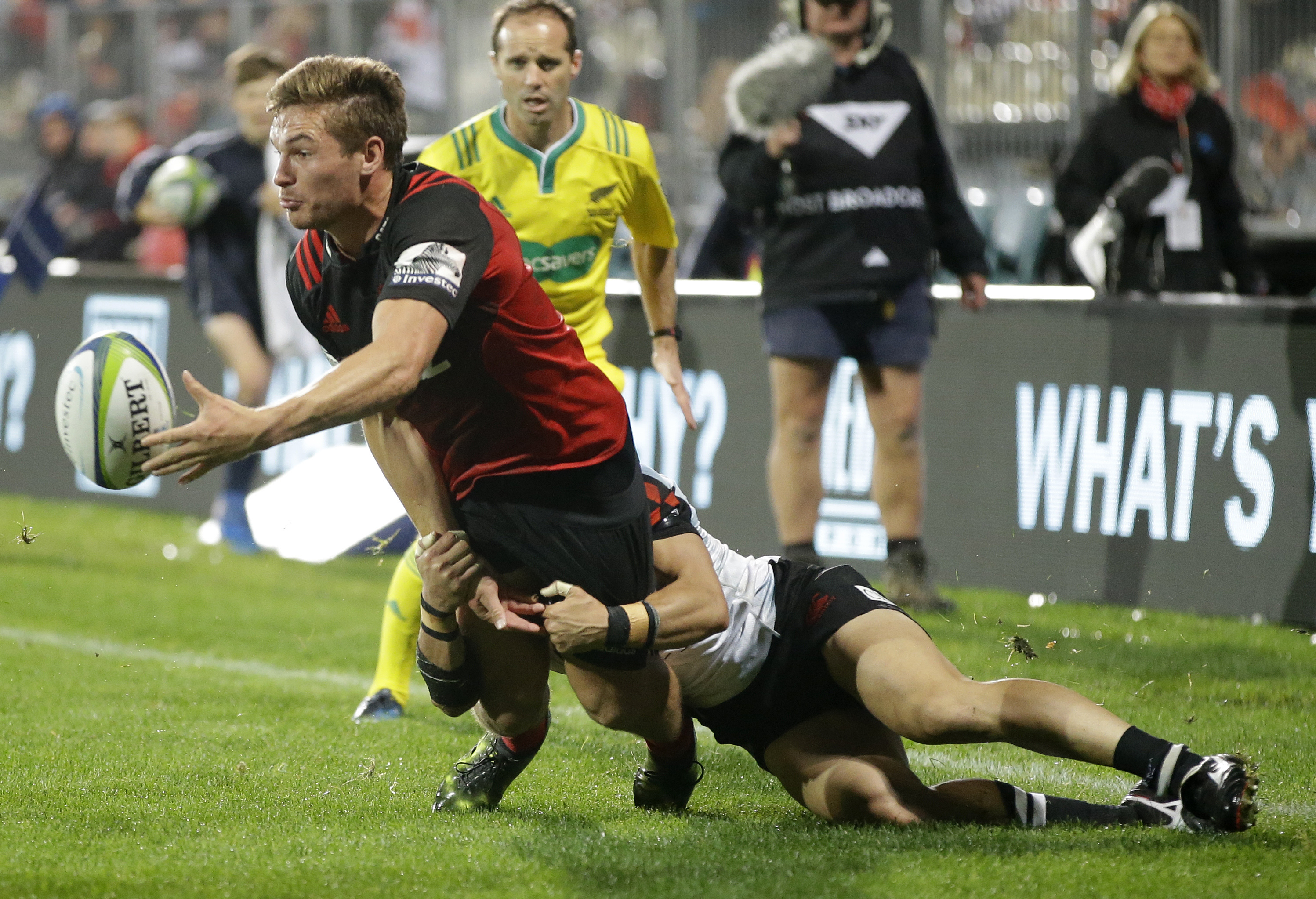 Crusaders George Bridge passes the ball as he is tackled by Sunwolves Takaaki Nakazuru during their Super Rugby match in Christchurch, New Zealand, Friday, April 14. (AP Photo/Mark Baker)