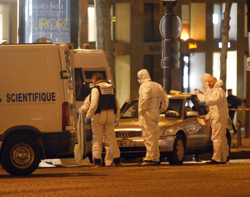 Forensic experts collect evidences from the car belonging to an attacker who killed a police officer on the Champs Elysees avenue in Paris, France, Friday, April 21, 2017. (AP Photo/Thibault Camus)