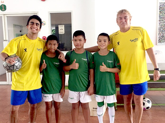 Lionel Izaaks (right) and Gabriel Albequerque (left) from the Samba Soccer academy in Pattaya pose with budding football stars at the Father Ray Children's Home, Wednesday, May 10.