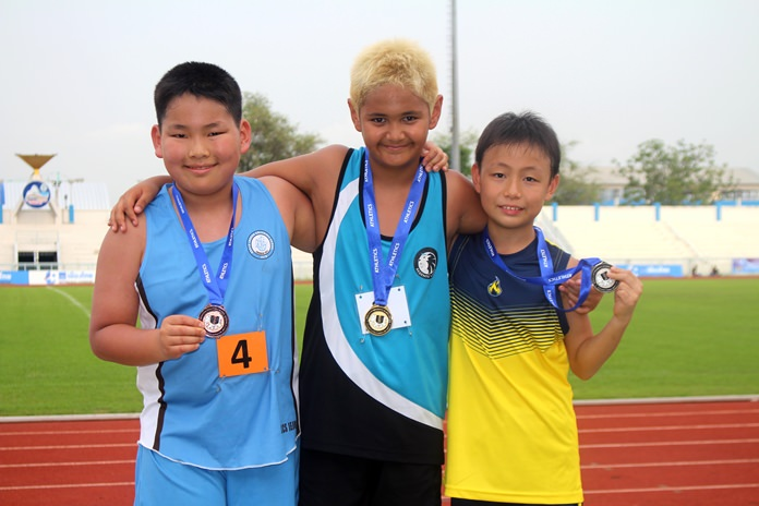 A trio of aspiring athletes pose for a photo during the track and field section of the Games.