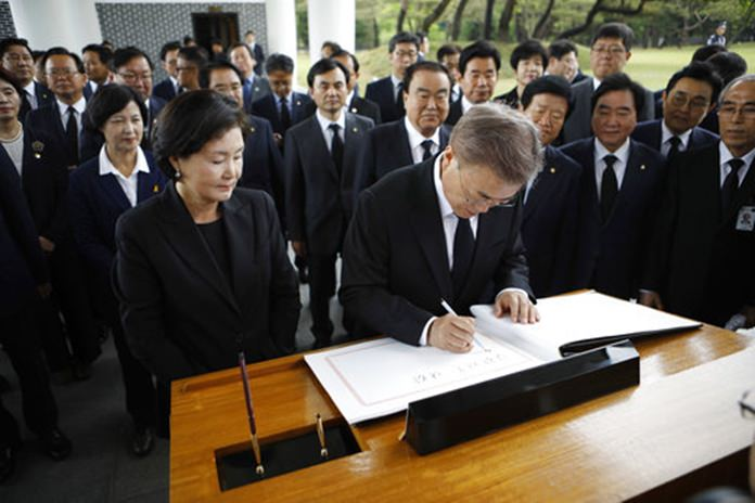 New South Korea's President Moon Jae-in, center, writes down a visitor's book at the National Cemetery in Seoul, South Korea Wednesday, May 10, 2017.(Kim Hong-ji/Pool Photo via AP)