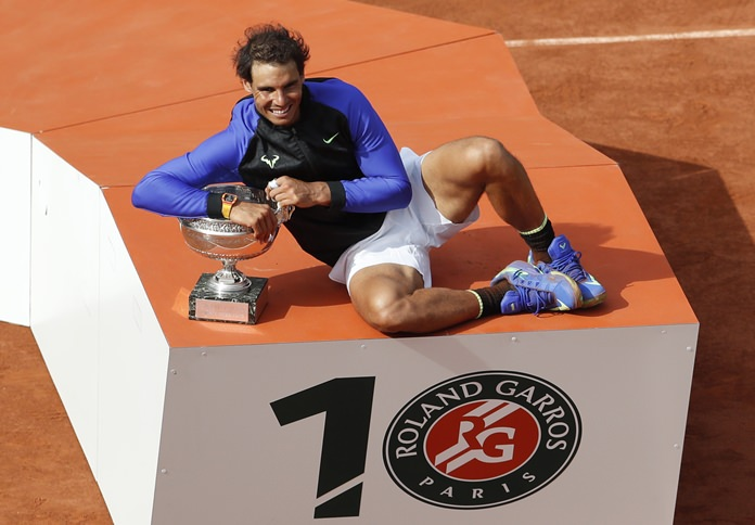 Spain's Rafael Nadal poses with the trophy after winning his tenth French Open title against Switzerland's Stan Wawrinka during the French Open tennis tournament at the Roland Garros stadium in Paris Sunday June 11