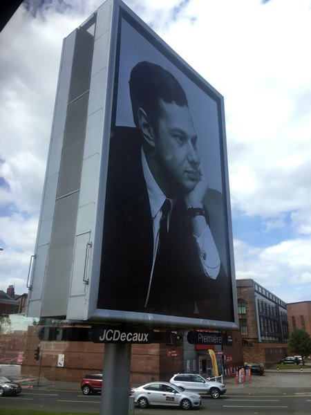 "Cars drive past a billboard showing the late Beatles manager Britain Epstein, created by artist Jeremy Deller as part of the ""Sgt. Pepper at 50"" festival, in Liverpool, England.. (AP Photo/Jill Lawless)"