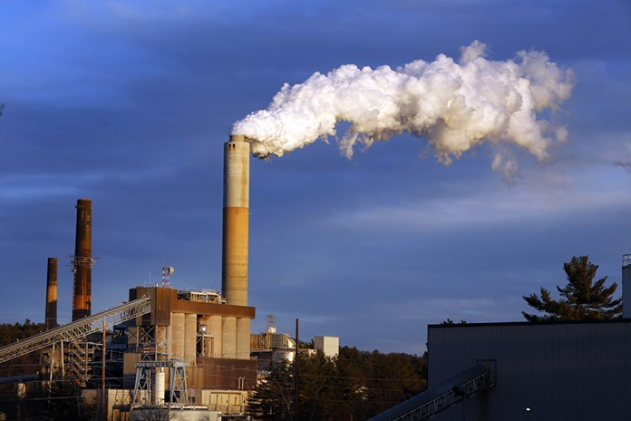 In this Jan. 20, 2015 file photo, a plume of steam billows from the coal-fired Merrimack Station in Bow, N.H. Earth is likely to hit more dangerous levels of warming even sooner if the U.S. pulls back from its pledge to cut carbon dioxide pollution because America contributes so much to rising temperatures, scientists said. (AP Photo/Jim Cole, File)