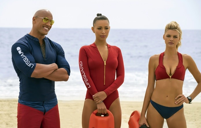 """This image shows (from left) Dwayne Johnson as Mitch Buchannon, Ilfenesh Hadera as Stephanie Holden and Kelly Rohrbach as CJ Parker in a scene from """"Baywatch."""" (Frank Masi/Paramount Pictures via AP)"""