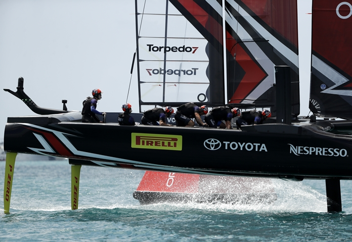 Peter Burling, helmsman for Emirates Team New Zealand, left, steers as they race against Oracle Team USA during the America's Cup match sailing competition Saturday, June 17, in the Great Sound of Bermuda. (AP Photo/Gregory Bull)