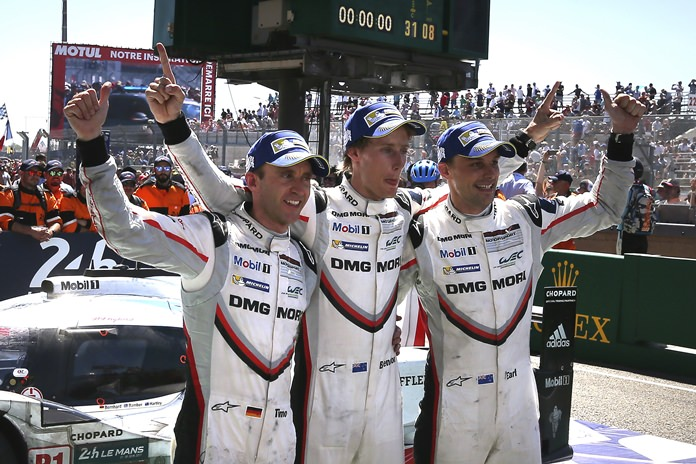 Drivers of the Porsche 919 Hybrid No2, from left to right, Brendon Hartley of New Zealand, Earl Bamber of New Zealand and Timo Bernhard of Germany gesture after winning the 85th 24-hour Le Mans endurance race, in Le Mans, western France, Sunday, June 18. (AP Photo/David Vincent)
