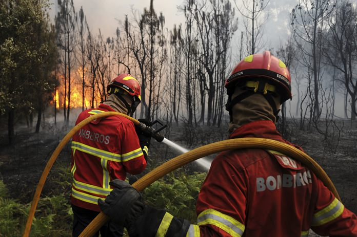 Portuguese firefighters work to stop a forest fire from reaching the village of Figueiro dos Vinhos central Portugal, Sunday, June 18. (AP Photo/Paulo Duarte)