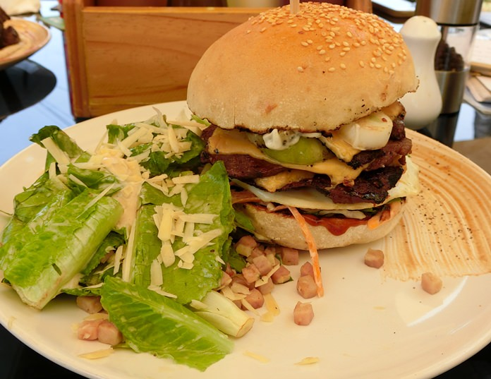 A very, very large beef burger with Caesar salad.