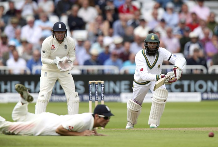 South Africa's Hashim Amla, right, sees his drive stopped by England's Alastair Cook, bottom left, during day one of the second cricket Test match between England and South Africa at Trent Bridge, Nottingham, England Friday July 14. (Nick Potts/PA via AP)