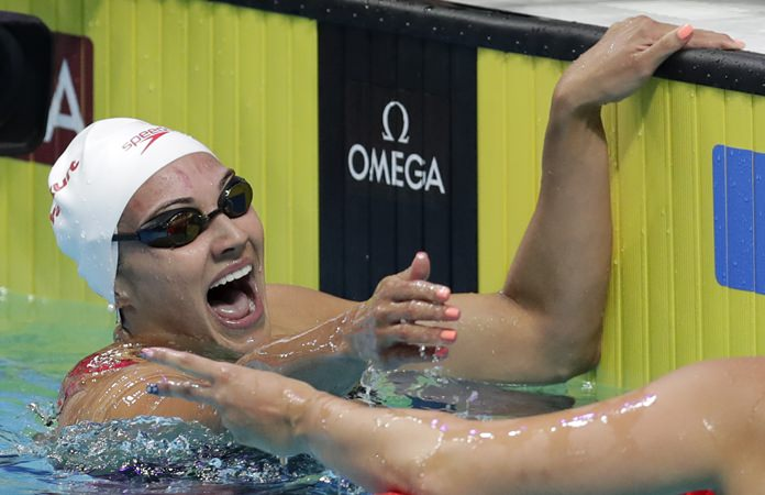 Canada's gold medal winner Kylie Jacqueline Masse celebrates after setting a new world record in the women's 100-meter backstroke final during the World Aquatics Championships in Budapest Hungary Tuesday July 25