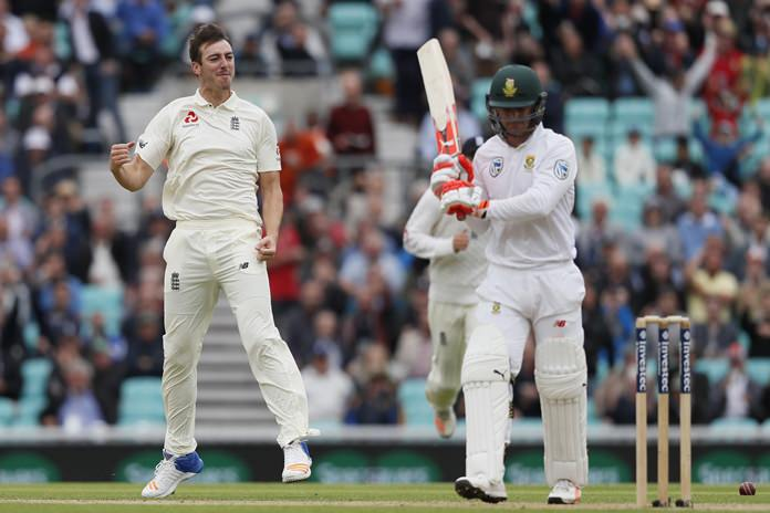 England's Toby Roland-Jones, left, celebrates taking the wicket of South Africa's Heino Kuhn, right, on the second day of the third test at The Oval cricket ground in London, Friday, July 28. (AP Photo/Kirsty Wigglesworth)