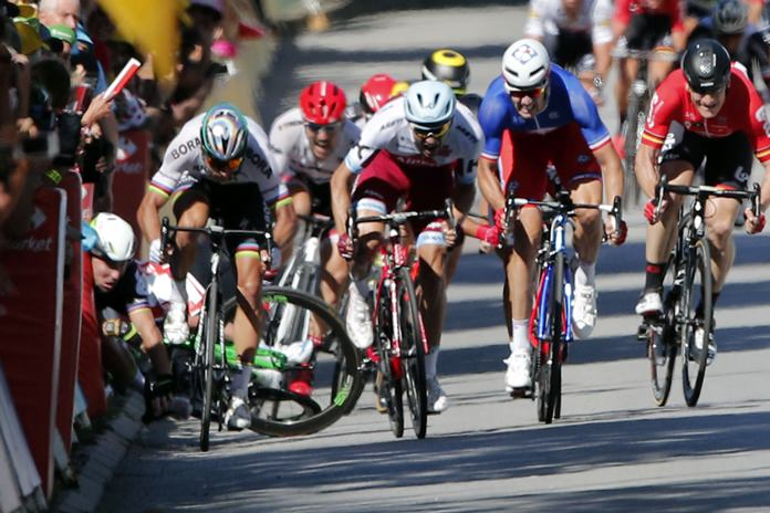 Britain's Mark Cavendish, left, crashes into the barriers during the sprint of the fourth stage of the Tour de France cycling race in Vittel, France, Tuesday, July 4. (AP Photo/Christophe Ena)