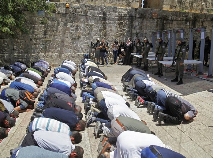 Israeli border police officers stand guard as Muslim men pray outside the Al Aqsa Mosque compound, in Jerusalem Sunday, July 16, 2017. (AP Photo/Mahmoud Illean)
