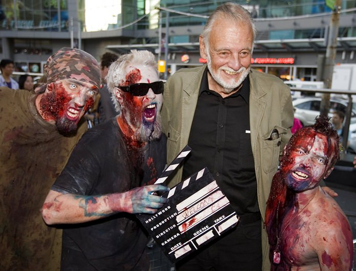 In this Sept. 12, 2009, file photo, director George Romero poses with some fans dressed as zombies after accepting a special award during the Toronto International Film Festival in Toronto. (Darren Calabrese/The Canadian Press via AP, File)