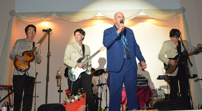Event organizer Tom Coghlan introduces the first set by the Beatles Tribute act.
