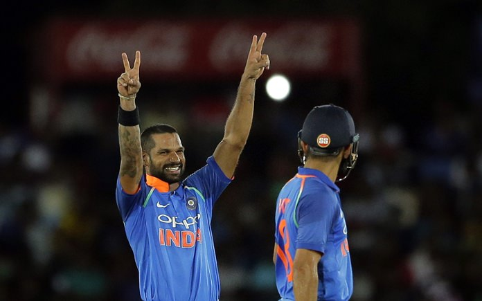 India's Shikhar Dhawan, left, gestures towards his team's dressing room after scoring a century during the first one-day international against Sri Lanka in Dambulla, Sri Lanka, Sunday, Aug. 20. (AP Photo/Eranga Jayawardena)
