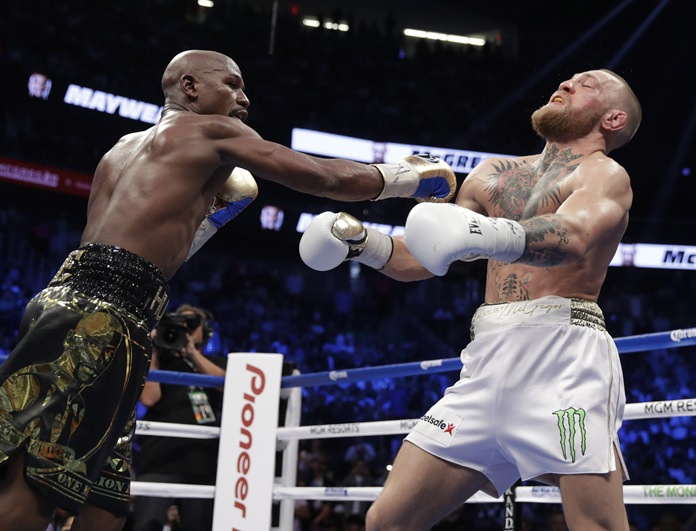 Floyd Mayweather Jr., left, hits Conor McGregor in their super welterweight boxing match Saturday, Aug. 26, in Las Vegas. (AP Photo/Isaac Brekken)