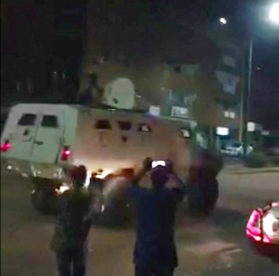 This image taken from video, early Monday, Aug. 14, 2017, shows an armoured vehicle driving down a street after an attack in Ouagadougou, Burkina Faso. (@Yabsi1er via AP)