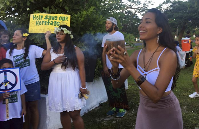 In this Aug. 14, 2017 file photo, Eva Aguon Cruz, 30, holds a cup with burnt flower as a ritual to call for protections from the spirits as about a hundred people gathered at Chief Kepuha Park in Hagatna, Guam for a rally for peace. (AP Photo/Tassanee Vejpongsa, File)