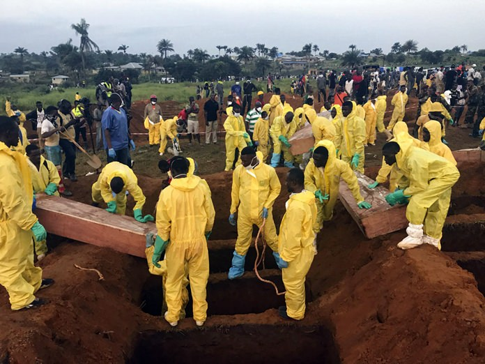 Volunteers handle a coffin during a mass funeral for victims of heavy flooding and mudslides in Regent at a cemetery in Freetown, Sierra Leone, Thursday, Aug. 17, 2017.(AP Photo/ Manika Kamara)