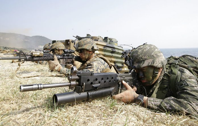 In this March 30, 2015, file photo, Marines of South Korea, right and the U.S aim their weapons near amphibious assault vehicles during the U.S.-South Korea joint landing military exercises as a part of the annual joint military exercise Foal Eagle between South Korea and the United States in Pohang, South Korea. (AP Photo/Lee Jin-man, File)