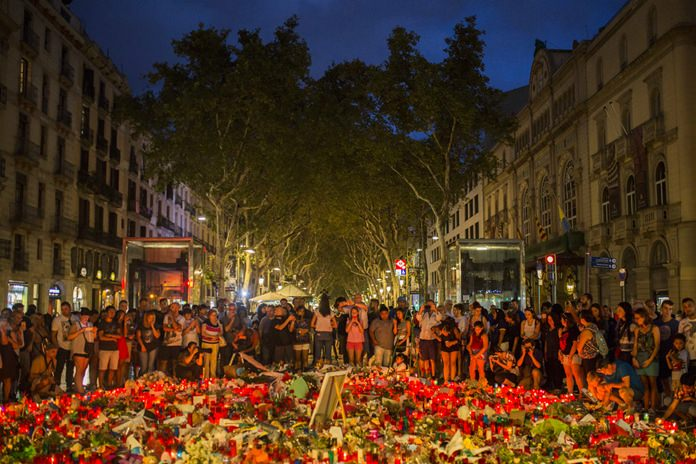 People stand next to candles and flowers placed on the ground, after a terror attack that left many killed and wounded in Barcelona, Spain, Sunday, Aug. 20, 2017. (AP Photo/Santi Palacios)