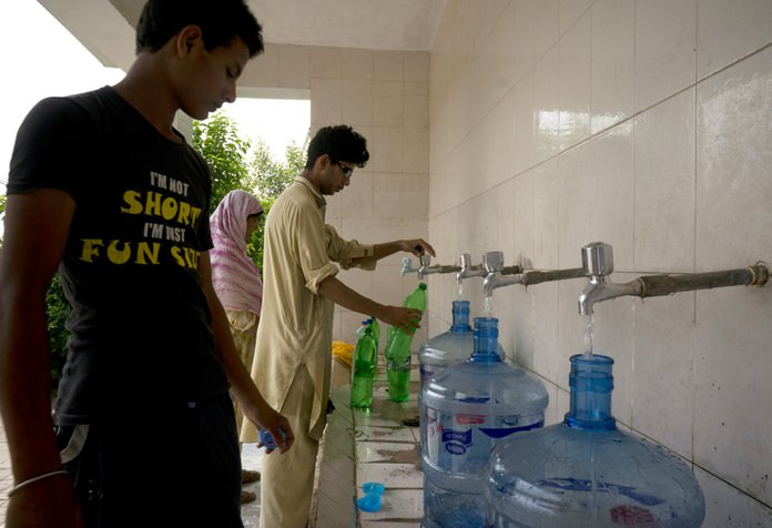 People at a filtration plant fill their bottles with water from a tube well, in Islamabad, Pakistan, Wednesday, Aug. 23, 2017. (AP Photo/B.K. Bangash)