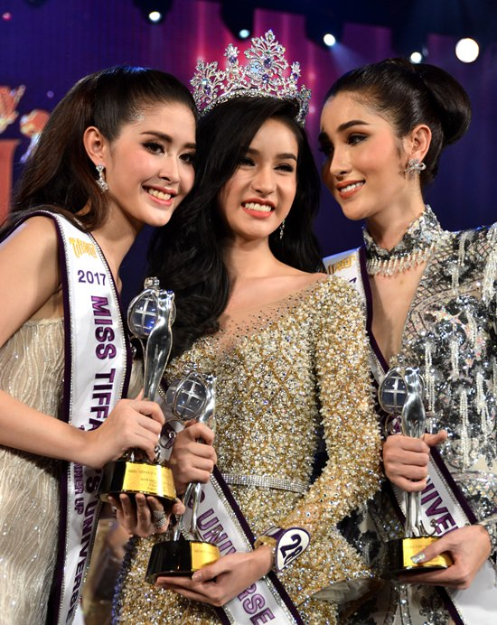 'Yoshi' Rinrada Turapan (center), wearing the 2017 Miss Tiffany crown, poses with first runner-up Kwanlod Rungrojampha (left) and Pimpasa Panupawinchok during the beauty pageant grand finals night at Tiffany's show theatre in Pattaya, Friday, August 25.