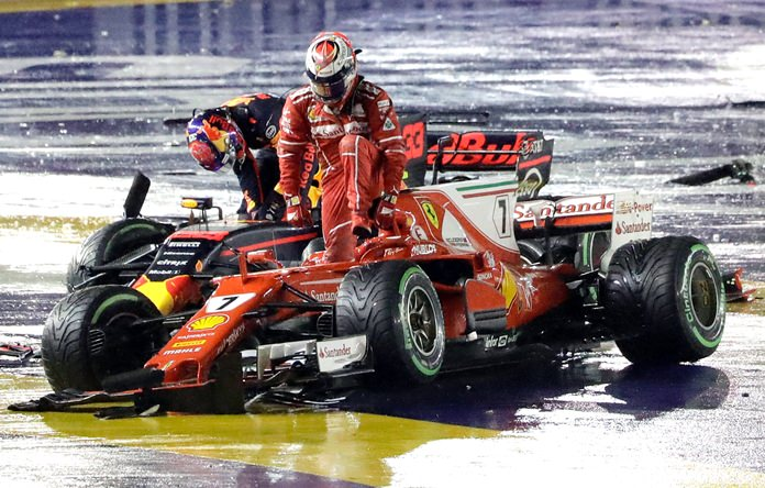 Ferrari driver Kimi Raikkonen (right) of Finland and Red Bull driver Max Verstappen of the Netherlands leave their cars after colliding at the start of the Singapore Formula One Grand Prix on the Marina Bay City Circuit Singapore, Sunday, Sept. 17. (AP Photo/Wong Maye-E)