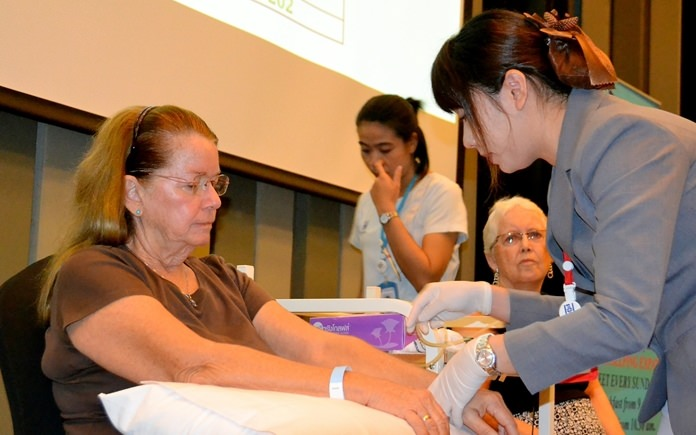 A nurse from PIH inserts a small laser tube into a vein of one of two PCEC volunteers for a one hour session to demonstrate the use of the Bio-Laser.