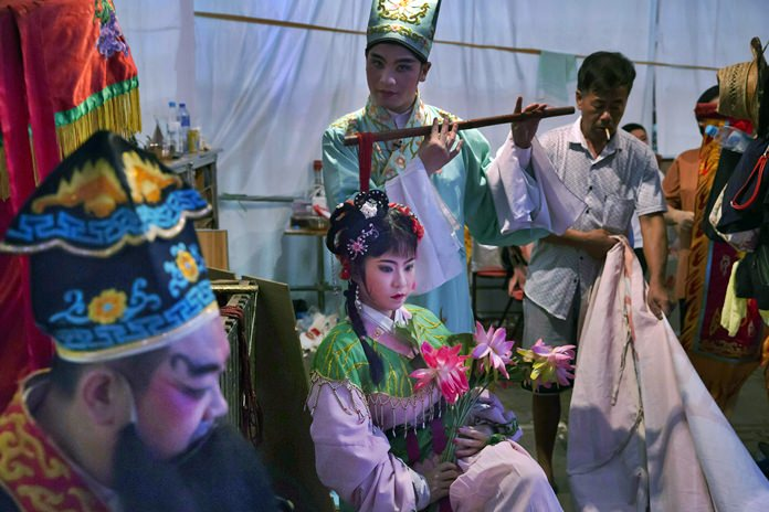 Chinese opera performers wait at a makeshift theater. (AP Photo/Kin Cheung)