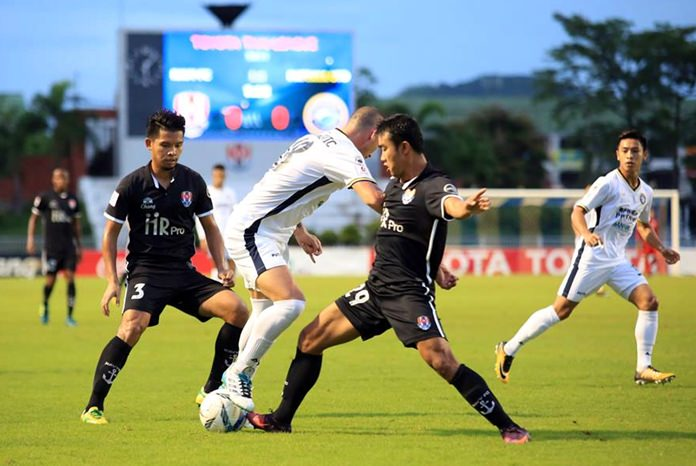 Pattaya United's Serbian striker Milos Stojanovic (centre) fights for the ball with Navy defenders during the first half of the Thai Premier League game between Pattaya United and Siam Navy FC at the Sattahip Navy Stadium in Sattahip, Sunday, Sept. 17.