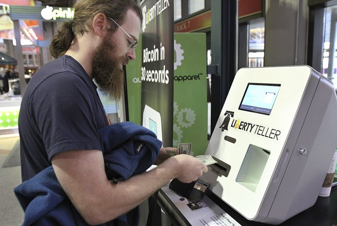 In this Monday, March 31, 2014, file photo, Tim McCormack, of Boston, inserts cash into a Liberty Teller ATM while purchasing bitcoins at South Station train station, in Boston. On Thursday, Sept. 14, 2017, Bitcoin tumbled 15 percent to about $3,300 against the dollar. (AP Photo/Steven Senne, File)