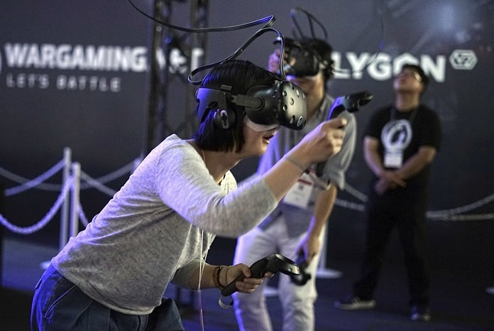In this Thursday, Sept. 21, 2017 file photo, visitors try out a game with a virtual reality headset device at the Tokyo Game Show in Chiba, near Tokyo. The Japanese video game industry is finding its way out of the doldrums by adapting new technology for decades-old titles. And that energy was evident at the annual game show. (AP Photo/Eugene Hoshiko, File)