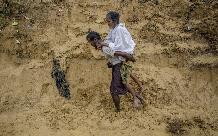 "In this Thursday, Sept. 21, 2017 file photo, Alishaan, a Rohingya Muslim man, carries his sick mother Aishya Khatoon to a hospital at Taiy Khali refugee camp, Bangladesh. More than 400,000 Rohingya Muslims have fled to Bangladesh since Aug. 25, when deadly attacks by a Rohingya insurgent group on police posts prompted Myanmar's military to launch ""clearance operations"" in Rakhine state. (AP Photo/Dar Yasin, File)"