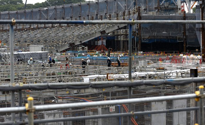 Laborers work at a construction site of new the national stadium in Tokyo, Tuesday, Sept. 12. (AP Photo/Shizuo Kambayashi)