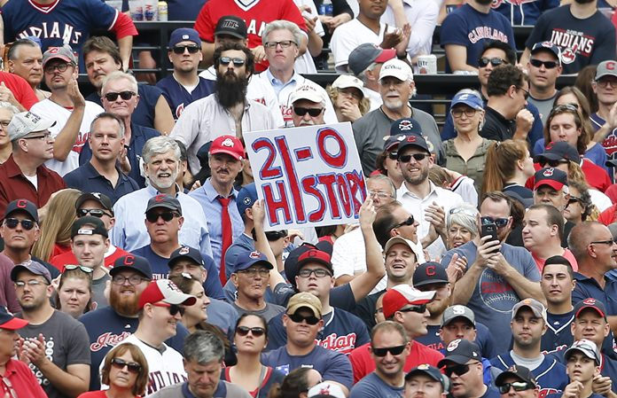 Cleveland Indians fans celebrate a 5-3 victory over the Detroit Tigers in a baseball game, Wednesday, Sept. 13, in Cleveland. The Indians set the American League record with 21 consecutive wins. (AP Photo/Ron Schwane)