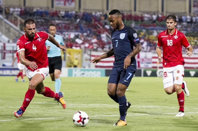 England's Raheem Sterling, center, is challenged by Malta's Steve Borg, left, during the World Cup group F qualifying match between Malta and England, at the Ta Qali stadium, in Valletta, Malta, Friday Sept.1. (AP Photo/Rene Rossignaud)
