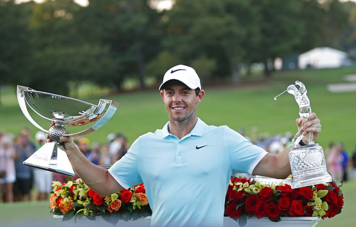 In this Sept. 25, 2016, file photo, Rory McIlroy poses with the trophies after winning the Tour Championship golf tournament and the FedEX Cup at East Lake Golf Club, in Atlanta. (AP Photo/John Bazemore, File)