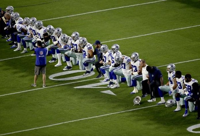 Members of the Dallas Cowboys, including owner Jerry Jones, take a knee before the national anthem ahead of a Monday Night Football game against the Arizona Cardinals, Sept. 25, in Glendale, Ariz. (AP Photo/Matt York). (Matt York/Associated Press)