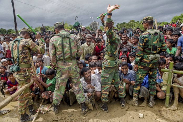 Bangladesh army soldiers stand guard as Rohingya Muslim men, who crossed over from Myanmar into Bangladesh, wait to receive aid during a distribution near Balukhali refugee camp, Bangladesh, Thursday, Sept. 28. (AP Photo/Dar Yasin)